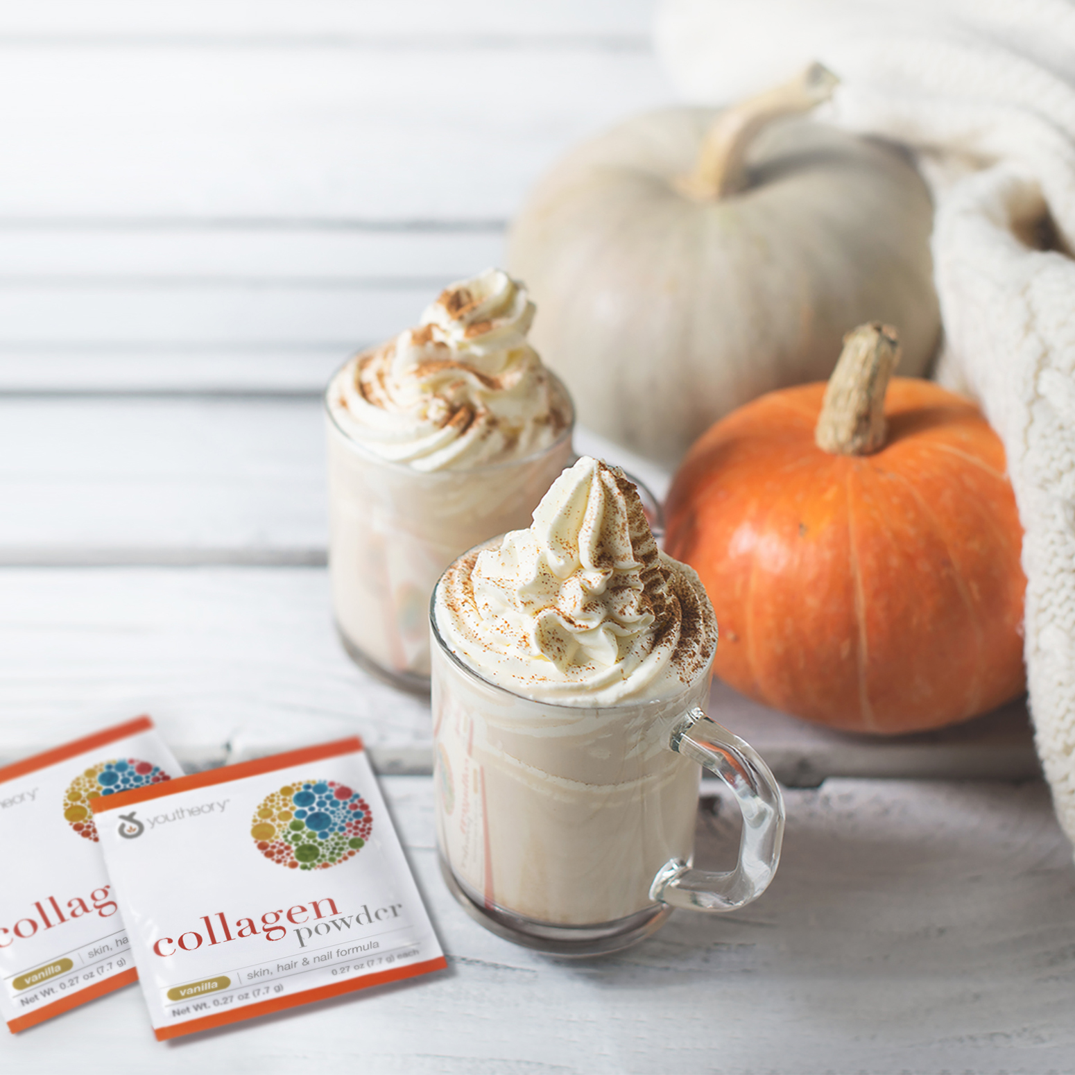 Collagen Powder packets next to Pumpkins spice latte with pumpkins and white cozy sweater over white wood texture.